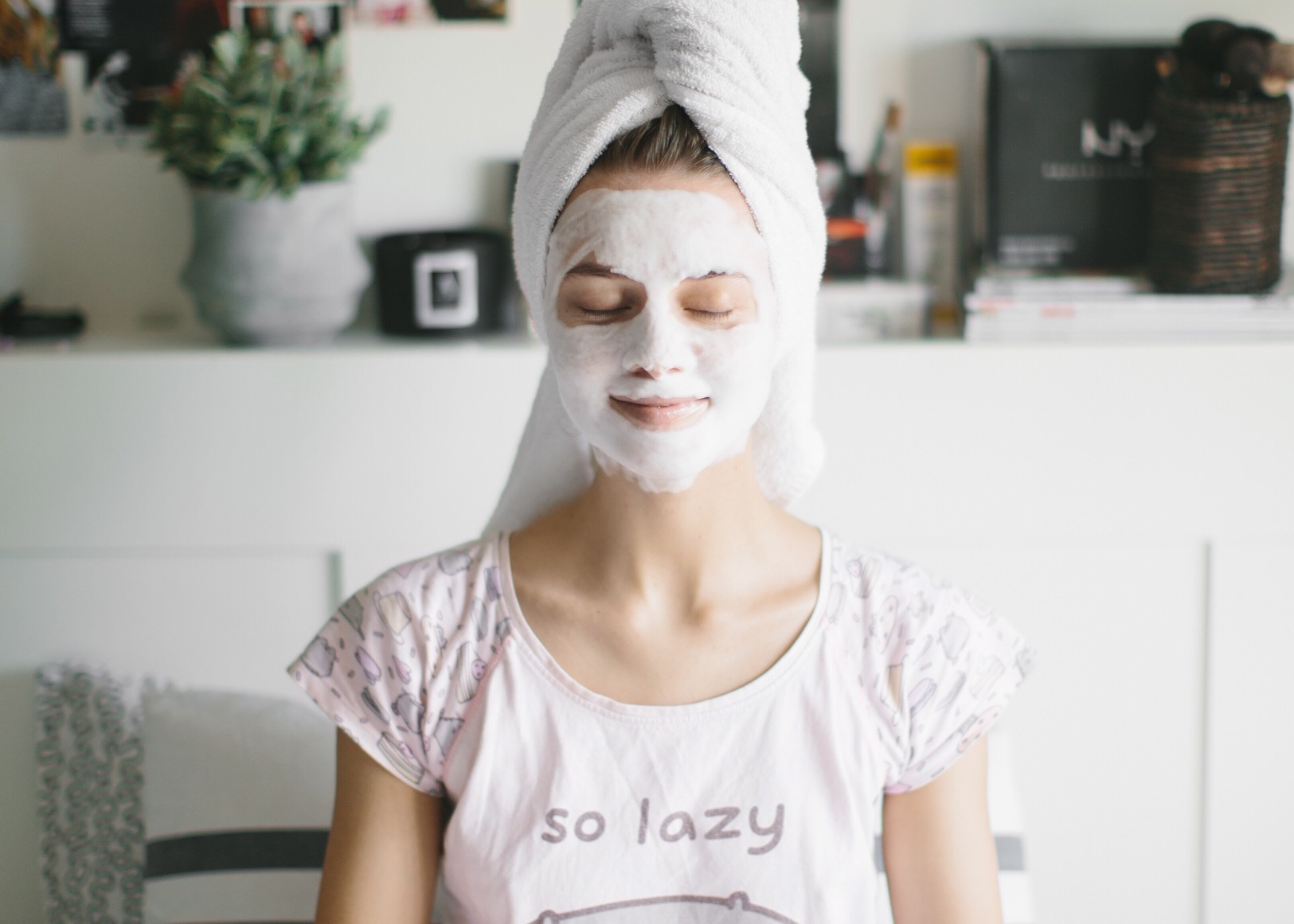 Woman with face pack on smiling on her bed