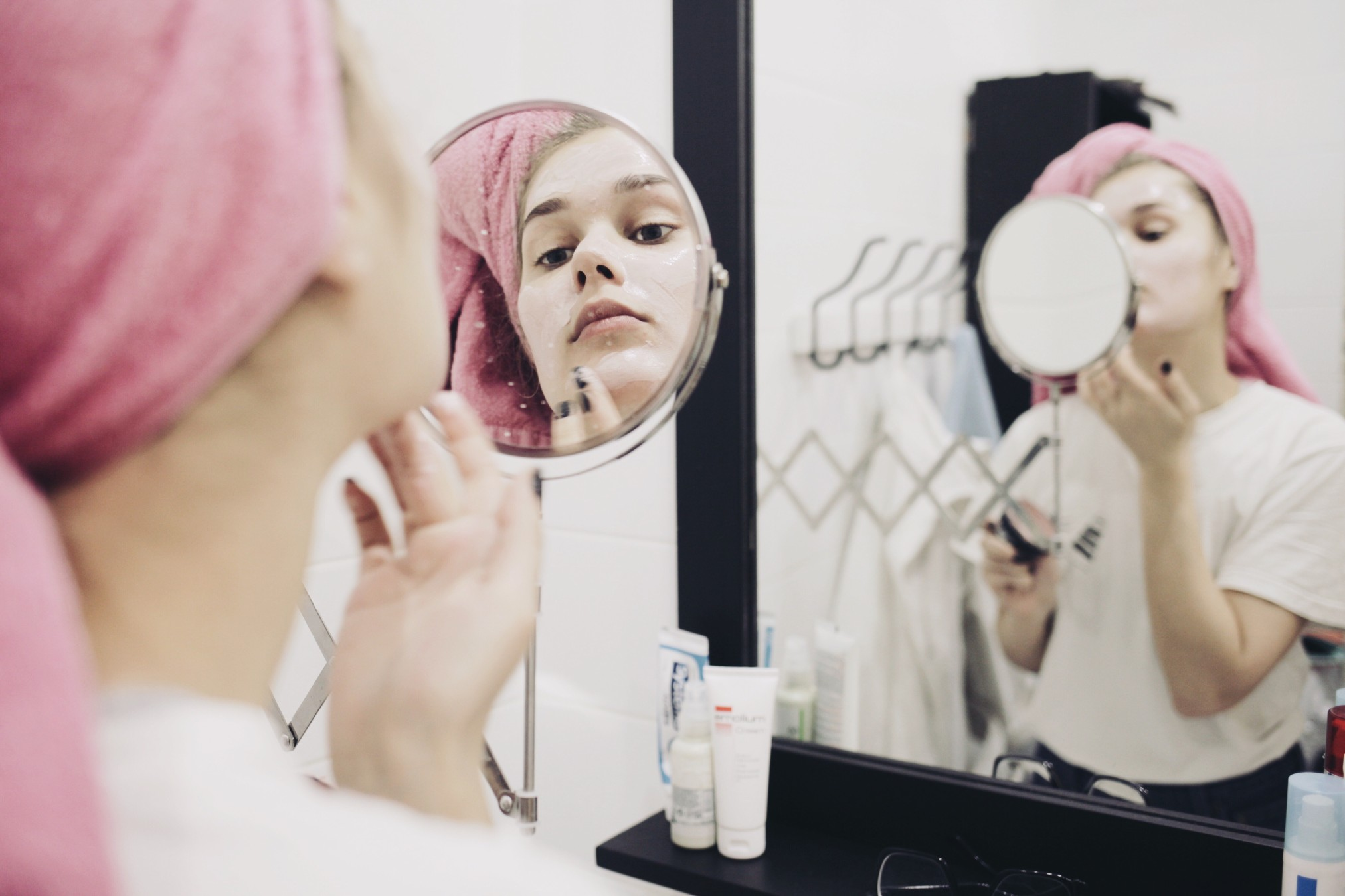 Imag of woman examining her face in the mirror - skin care in periods